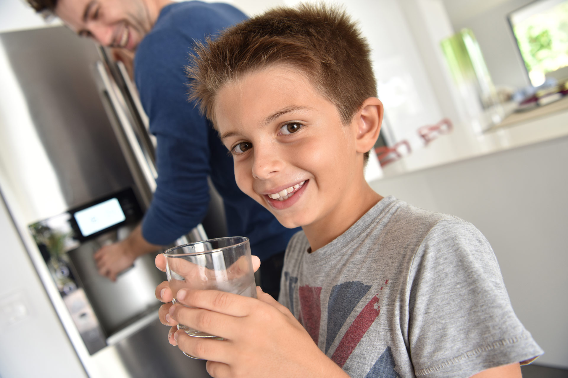 Boy drinking water in kitchen with dad behind him