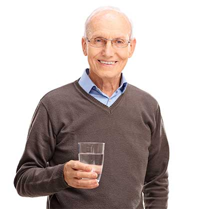 Old man holding a glass of clean water