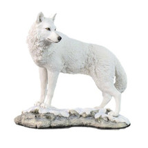 White Wolf Sculpture on Snowy Ground Looking Back