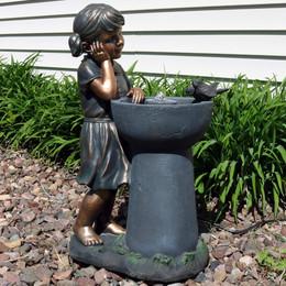 little girl admiring water spout outdoor garden water fountain outdoor