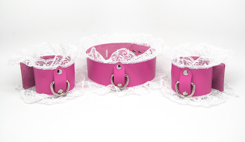 A pink leather collar with white lace, d-ring and matching cuffs.