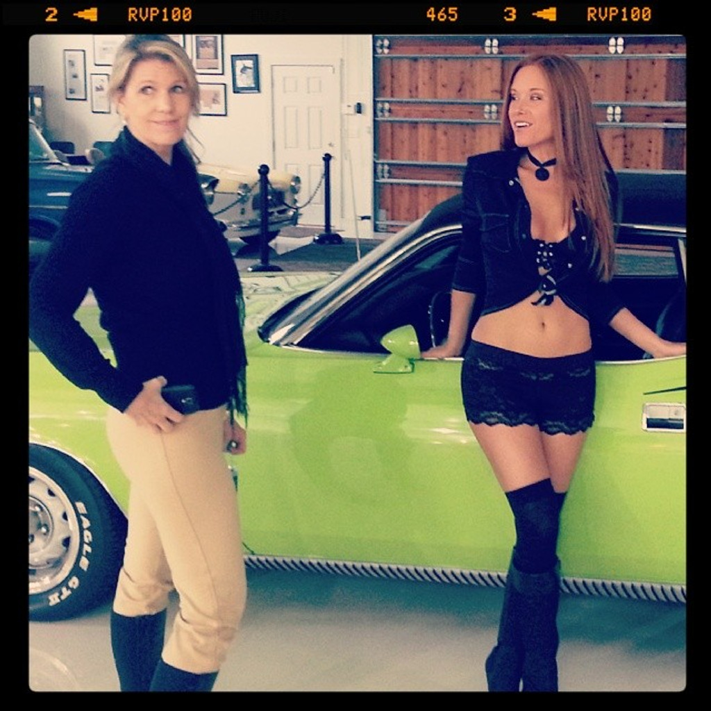 April and Tracy in front of a bright green 70s hemi cuda.  Tracy is wearing black lace boxer shorts and lace cami with a western sheer top.
