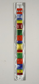 """Wall Totem in Spectrum by Hands On Art Glass. 2""""x24"""", fused glass on aluminum. Please call our galleries to see which pieces are currently on hand."""