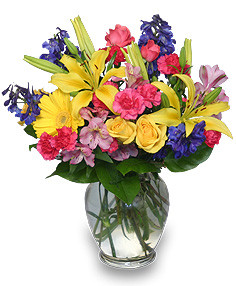 Rainbow of blooms showcases gerber daisies, yellow roses, delphinium, hot pink mini carnations, pink spray roses, pink alstroemeria and foliage in a ginger vase in Rockville MD, Palace Florists