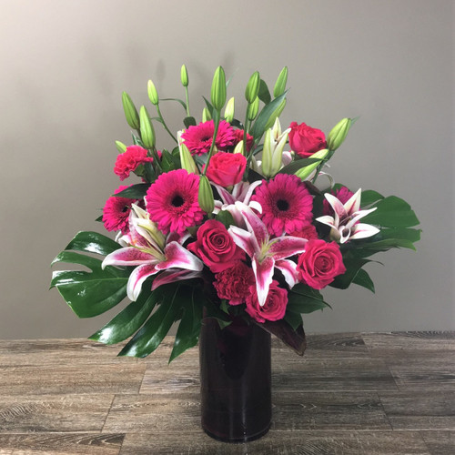 Haute Romance showcases roses, gerbers, lilies, ti leaves and fabulous foliage in a tall cylinder hand designed in Rockville MD, Palace Florists.