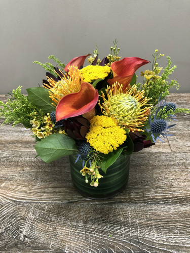 Cool Nights showcases callas, protea, thistle and other beautiful flowers in a clear cylinder with leaf wrap in Rockville MD, Palace Florists