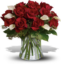 One dozen red roses accented with half dozen miniature white calla lilies accentented with assorted greenery in a vase in Washington DC and Rockville MD, Palace Florists