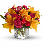 Uniquely Chic showcases orange roses, hot pink roses, spray roses, carnations, orange asiatic lilies and bear grass in a clear glass cube in Washington DC and Rockville MD, Palace Florists