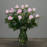 One Dozen Royal Roses Pink  accented with wax flower, coils of bear grass and beautiful foliage in clear glass vase in Washington DC and Rockville MD, Palace Florists