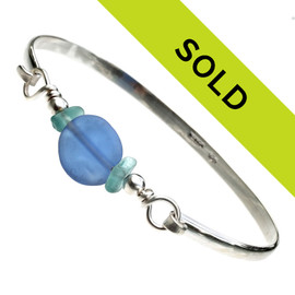 A medium blue handmade lampwork bead is set between two pieces of tropical aqua sea glass in this solid sterling bangle bracelet.