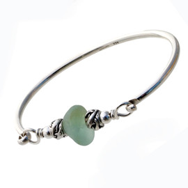 A thick and mixed seafoam green sea glass combined with dolphin beads on a full round solid sterling bangle bracelet.