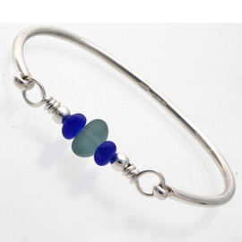Aqua sea glass from England set on a fully round solid sterling bangle bracelet. The blue frosted glass beads mimic sea glass and make this a stunning combination.