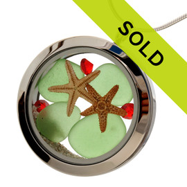 Green sea glass and vivid red gemstones make this a great locket necklace for the holidays. Two starfish and real beach sand make this a holiday beach treat.