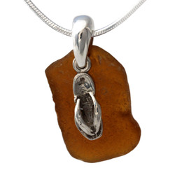 A simple but bright and old amber brown sea glass piece set on a solid sterling professionally handcast bail and finished with a flip flop charm!