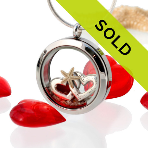 A Small piece of natural beach found ruby red sea glass combined with a real starfish, beach sand and a double heart sterling silver charm for your own personal beach on the go!