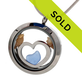Blue sea glass pieces combined a large silver heart in this sea glass locket necklace.
