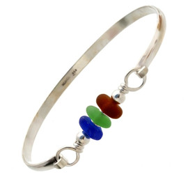 Three pieces of beach found sea glass in brown, vivid green and a rich cobalt blue on this solid sterling silver half round sea glass bangle bracelet.