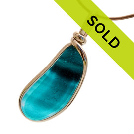 Intense mixed teal or aqua long and large sea glass piece found on the beaches of Seaham England set in our Original Wire bezel© sea glass pendant setting in 14K Rolled Gold.