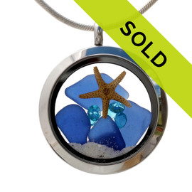 Blue sea glass pieces combined with a real starfish in this sea glass locket necklace. Aquamarine gems make this a great gift for a March Birthday.
