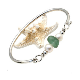 A thick piece of deep seafoam green sea glass combined with genuine fresh water pearls on a solid sterling bangle bracelet.