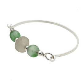 A thick pure white sea glass center bead and two recycled green glass beads set with sterling details on a solid sterling flat bangle bracelet.