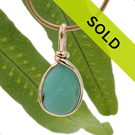 A nice piece of deep seafoam or aqua green with in our signature Original Wire Bezel© in gold pendant setting that leaves both front and back open and the glass unaltered from the way it was found on the beach. Sorry this sea glass jewelry piece has been sold!