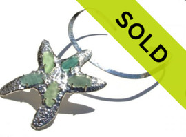 Sorry This Item has been SOLD  5 pieces of rare sea glass in aqua sea green and varying hues prong set on a totally hand crafted sterling starfish.  The starfish starts as a solid flat sheet of 20 gauge sterling and is cut and hammered on the opposite side to create the spines of the star. 20 prongs were then hand made and soldered in place to encapsulate this rare sea glass.  This piece comes on a complimentary hammered 4.6 mm solid sterling open oval collar that can fit any body frame.  We are unable to recreate this piece.