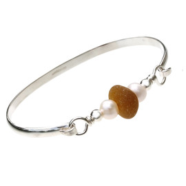 Beautiful honey colored beach found sea glass combined with real cultured pearls on this solid sterling silver half round sea glass bangle bracelet.