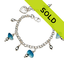 4 pieces of genuine beach found sea glass in a flashed aqua blue and white on a totally solid sterling silver bracelet finished with a sterling heart charm.  Sorry this sea glass jewelry piece has been sold!