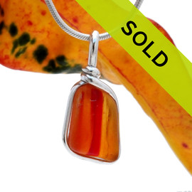 A once in a lifetime piece of large ORANGE art sea glass is set in our Original Wire Bezel© pendant setting.