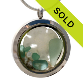 Genuine seafoam green and aqua sea glass pieces combined with a real sandollar and real beach sand in this 30MM stainless steel locket. Sorry this sea glass jewelry piece has been sold!