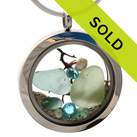 Genuine seafoam green and aqua sea glass pieces combined with a real sea fan, pearls , aquamarine gems and real beach sand in this 35MM stainless steel waterproof locket. Sorry this piece has been sold!