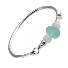 A center piece of perfect round aqua sea glass nestled between two 1960's vintage beads on a round solid sterling bangle bracelet.