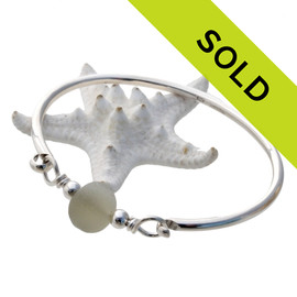 A thick piece of off white sea glass combined with sterling beads on a solid sterling bangle bracelet. Sorry this sea glass jewelry piece has been sold!