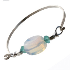 A large sea opal glass bead nestled between tow pieces of vivid aqua sea glass on a thin flat bangle bracelet.