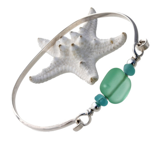Two pieces of beach found sea glass in aqua on this solid sterling silver half round sea glass bangle bracelet. The center bead is handmade by a glass artist and resembles bright green sea glass.
