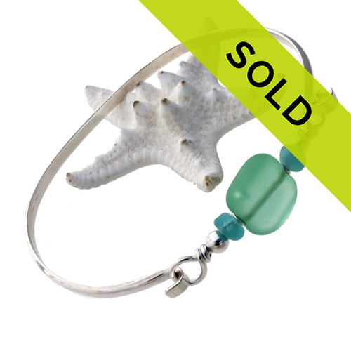 Two pieces of beach found sea glass in aqua on this solid sterling silver half round sea glass bangle bracelet. Sorry this sea glass jewelry selection is no longer available.