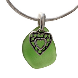 A perfect piece of natural green sea glass set on a solid sterling hand cast bail with a sterling silver heart in hearts charm.