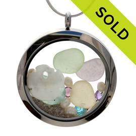 Genuine sea and pale green lavender, yellow and aqua sea glass combined with a real shells, sandollar, pearls, real beach sand , and crystal gems  in this JUMBO 35MM stainless steel locket. Sorry this Sea Glass Locket is no longer available.