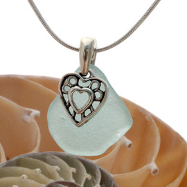 A nice piece of natural pure aqua sea glass set on a solid sterling hand cast bail with a sterling silver heart surrounded by hearts charm.