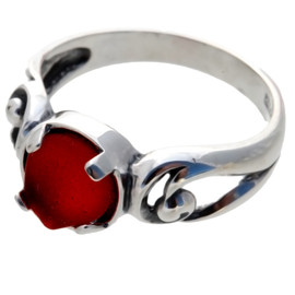 An unaltered glowing ruby red sea glass piece set in a simple sterling swirl ring.