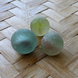 A trio of beach found sea glass marbles.