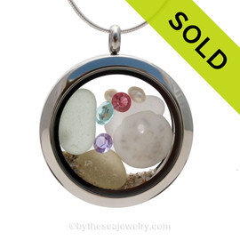 Another stunning Genuine pale vivid green, lavender, yellow sea glass combined with a real tiny sandollar, pearls, real beach sand, and crystal gems in this stainless steel locket.