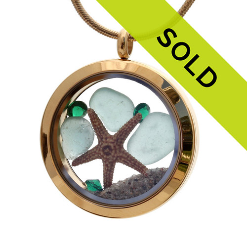 A stunning goldtone stainless steel locket necklace with aqua blue sea glass pieces a real baby starfish and emerald green gems for a may birthstone. Sorry this sea glass jewelry piece has been sold!