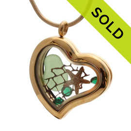 A stunning goldtone stainless steel locket necklace with a green sea glass piece a real baby starfish and emerald green gems for a may birthstone. SOLD, Sorry this Sea Glass Jewelry selection is no longer available.