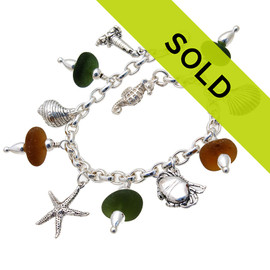 5 pieces of top quality Victorian English Sea Glass in amber and green combined with solid sterling beach inspired charms in a totally solid sterling silver bracelet.  All solid sterling charms that will remind you of your time at the beach! Sorry this sea glass jewelry item has been sold!