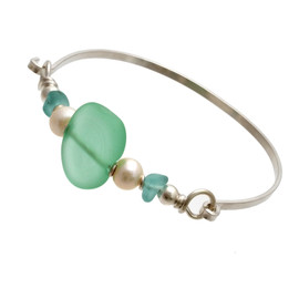 Two pieces of beach found sea glass in aqua on this solid sterling silver thin sea glass bangle bracelet. The center bead is handmade by a glass artist and resembles bright green sea glass. Finished in genuine pearls.