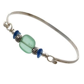 Two pieces of beach found sea glass in bright blue on this solid sterling silver sea glass bangle bracelet. The center bead is handmade by a glass artist and resembles bright green sea glass. Finished with sea life beads that have images of a crab, starfish and a sea gull.