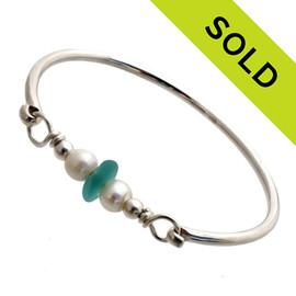 A vivid tropical aqua sea glass piece from Hawaii are combined with a two genuine fresh water pearls on a solid sterling bangle round bracelet. Sorry this Sea Glass Bracelet has been SOLD!