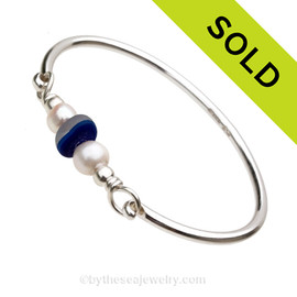 Mixed blue beach found Victorian era sea glass combined with real cultured pearls on this solid sterling silver half round sea glass bangle bracelet.  Sorry, this Sea Glass Jewelry selection has been sold!